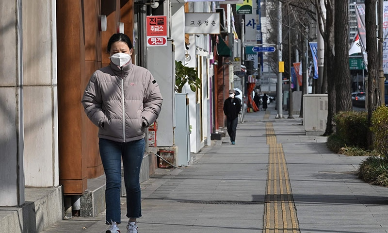 A woman wearing a face mask walks along a sidewalk in Daegu on February 27. — AFP