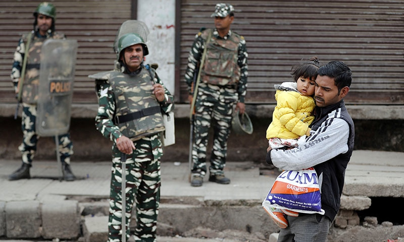 A man carrying a child walks past security forces in a riot affected area following clashes between people demonstrating for and against a new citizenship law in New Delhi, India on February 27. — Reuters