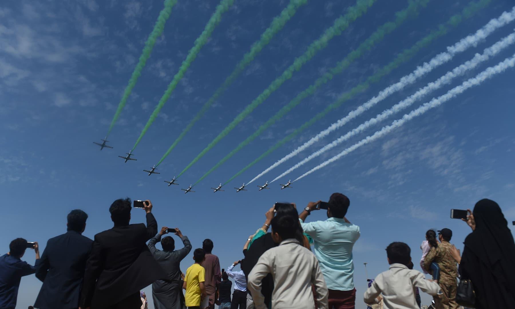 People watch Pakistani jets perform aerobatic manoeuvres in Karachi. — AFP