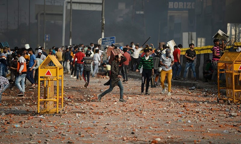 This file photo from Feb 24 shows demonstrators gathered along a road scattered with stones following clashes between supporters and opponents of a new citizenship law in New Delhi. — AFP