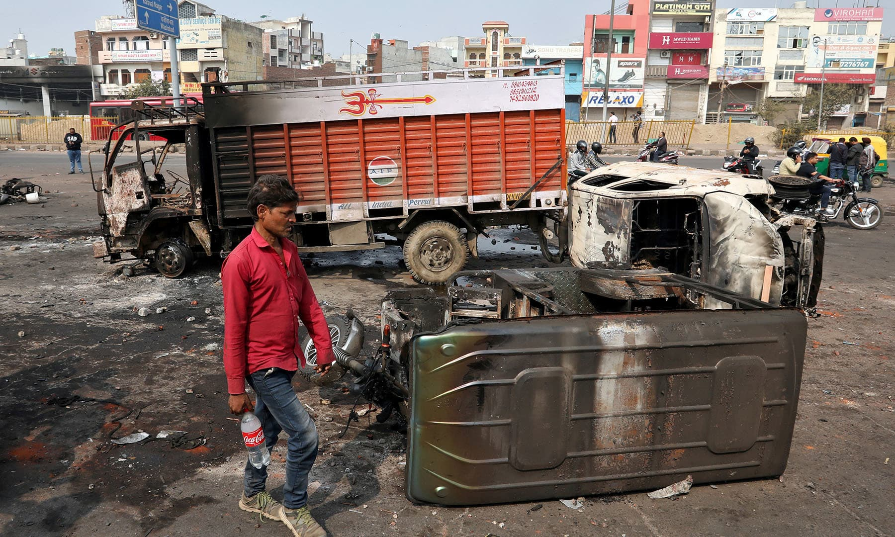A man walks past damaged vehicles after they were set on fire by a mob in a riot affected area after clashes erupted between people demonstrating for and against a new citizenship law in New Delhi,  February 26. — Reuters