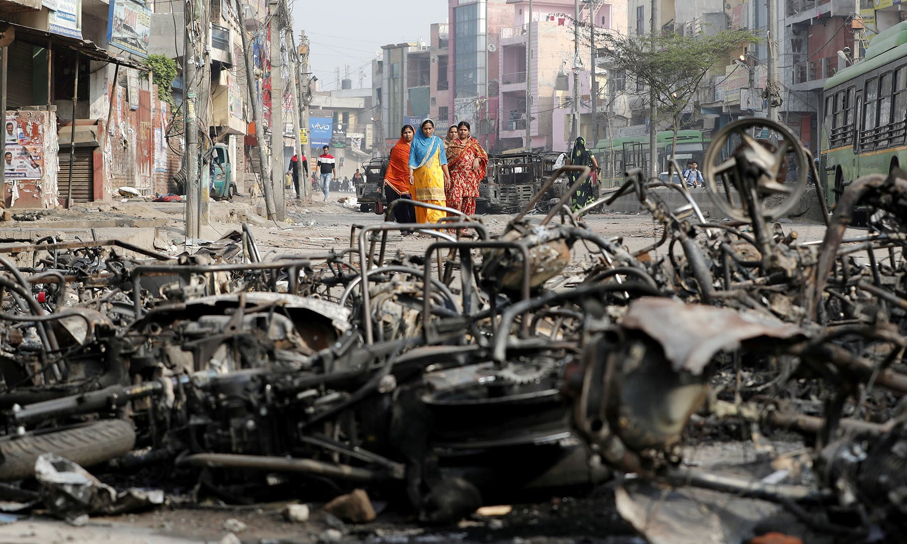 Women walk past charred vehicles in a riot affected area following clashes between people demonstrating for and against a new citizenship law in New Delhi, India on February 27. — Reuters