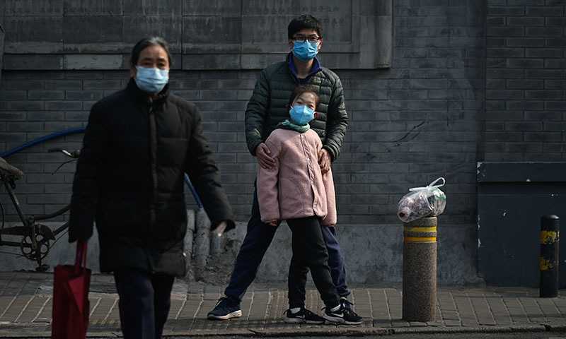 A man and a girl wearing face masks wait to cross a street in Beijing on February 28. — AFP
