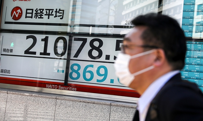 A man wearing a protective face mask, following an outbreak of the coronavirus, walks past a screen showing Nikkei index, outside a brokerage in Tokyo, Japan on February 28. — Reuters