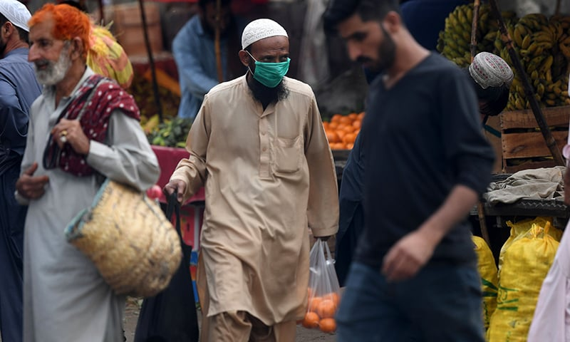 A resident wears a face mask at a market in Karachi on February 28. — AFP