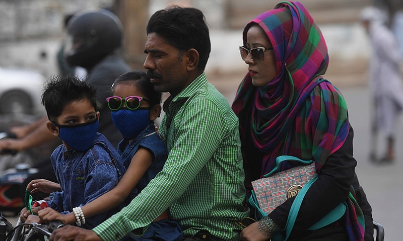 Commuters wear face masks on a street in Karachi on February 28. — AFP