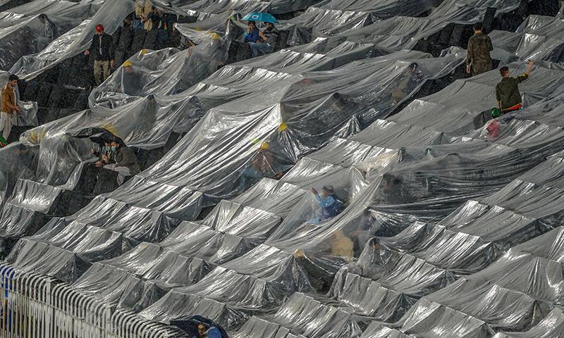بارش کے سبب راولپنڈی کرکٹ اسٹیڈیم میں شائقین نے خود کو ڈھکا ہوا ہے — فوٹو: اے ایف پی