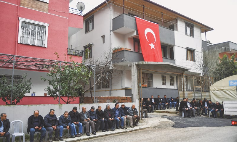 HATAY (Turkey): Mourners sit outside the home of a Turkish soldier killed in Syria.—AP