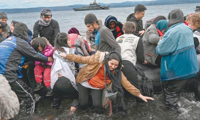 Lesbos (Greece): A woman makes her way as a dinghy with 54 Afghan refugees lands on this Greek island  on Friday.—AFP