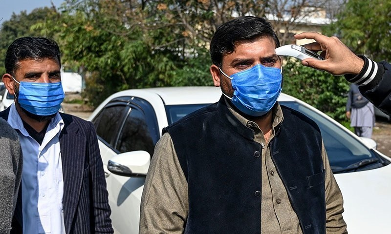An official of Pakistan-based Chinese company (R) uses a thermo gun to check the temperature of the company's drivers, in Islamabad on January 30, 2020, after instructions from Pakistani authorities to take preventive measures against the coronavirus. - A virus similar to the SARS pathogen has killed 170 people and spread around the world since emerging in a market in the central Chinese city of Wuhan. (Photo by Aamir QURESHI / AFP) — AFP or licensors