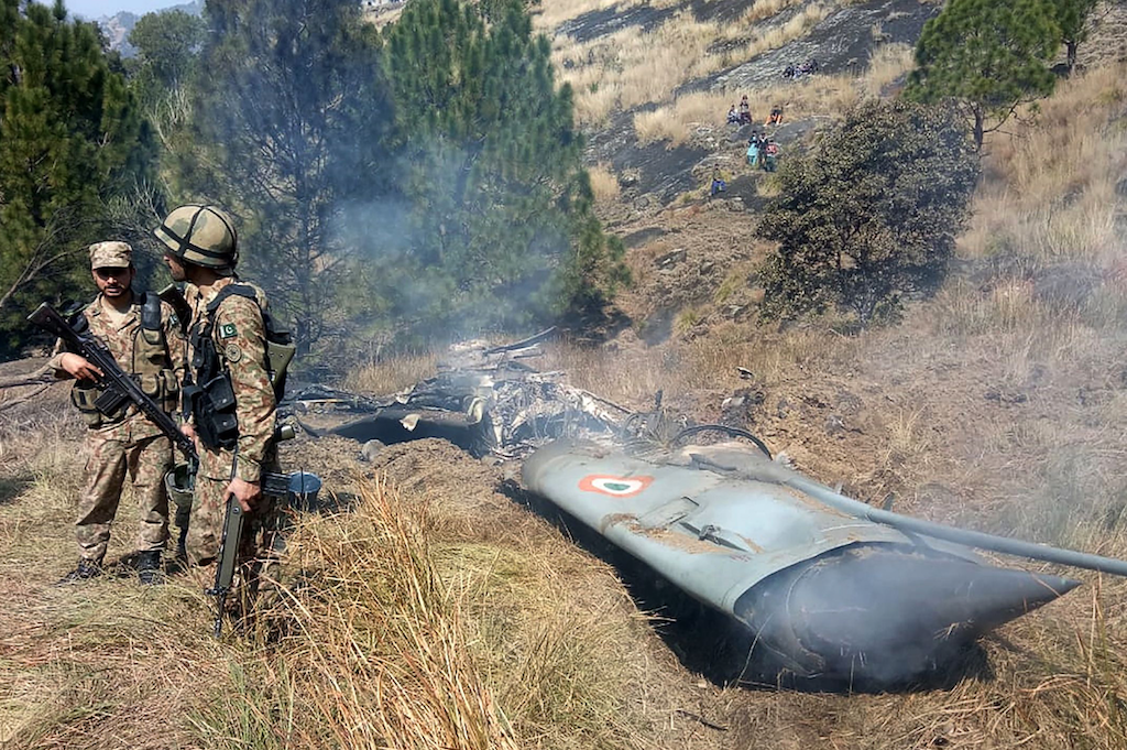 Pakistani soldiers stand next to the wreckage of an Indian fighter jet shot down in near the Line of Control on February 27, 2019 | STR/AFP