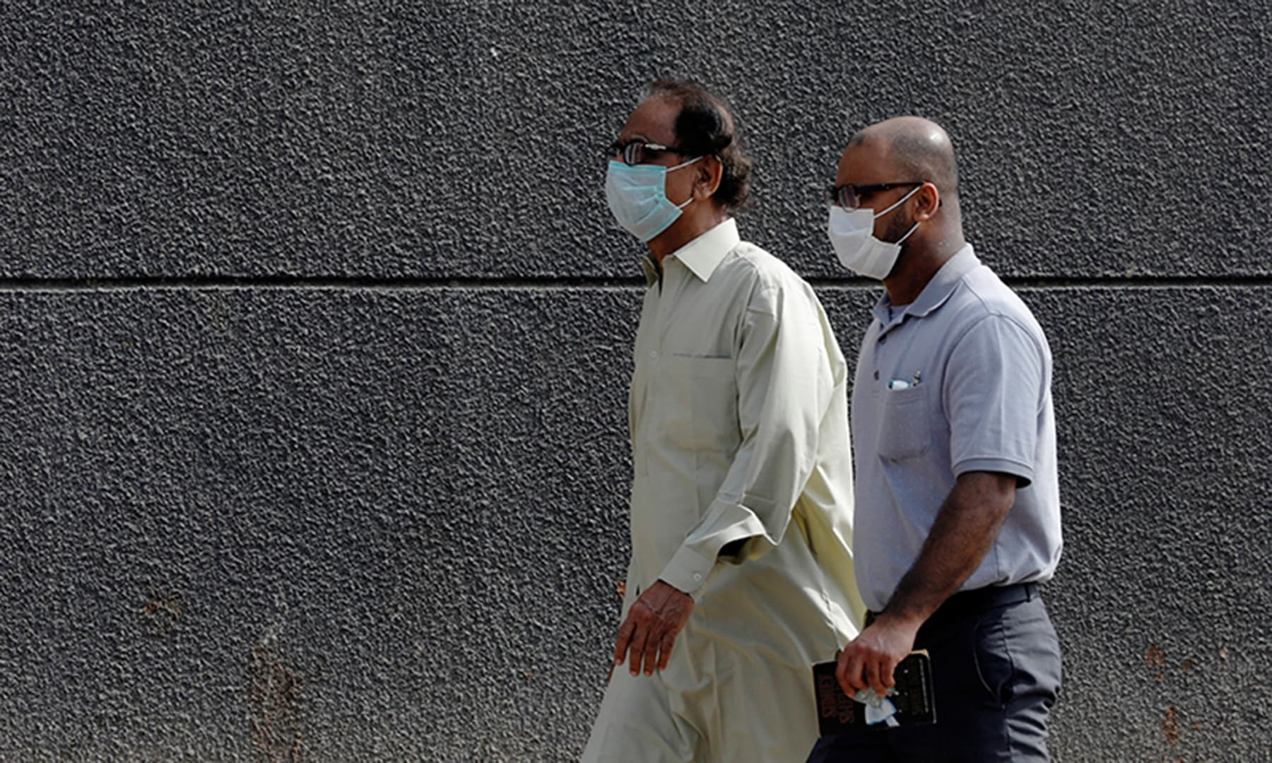 Men walk with face masks as a preventive measure along a sidewalk in Karachi, Pakistan on February 28. — Reuters/File