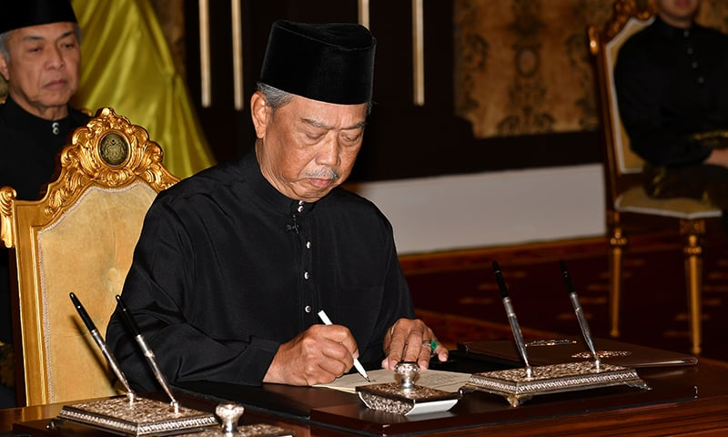 Muhyiddin Yassin signs a document during swearing-in ceremony as Malaysia's prime minister in Kuala Lumpur, Malaysia, on March 1.  — Malaysia Information Department/Famer Roheni/Handout via Reuters