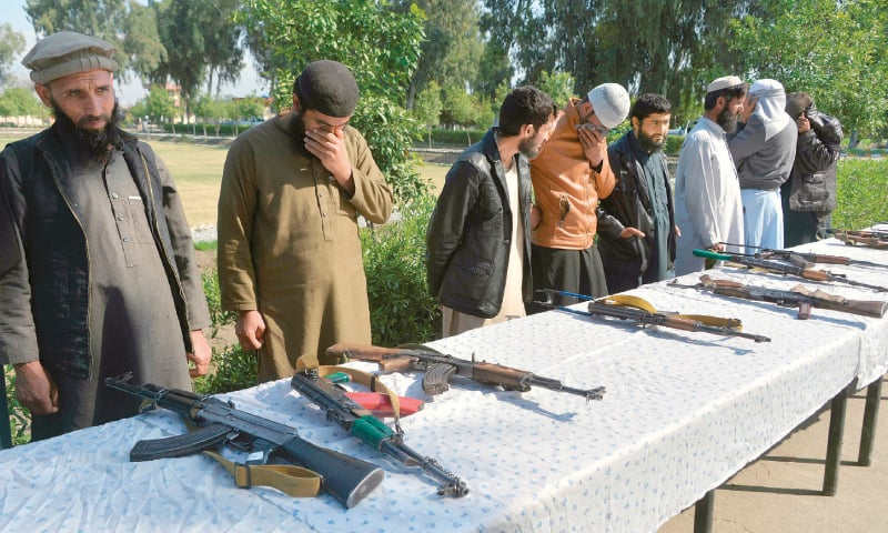 JALALABAD: Taliban fighters stand beside the weapons they handed over to the authorities at a ceremony on  Sunday.—AFP