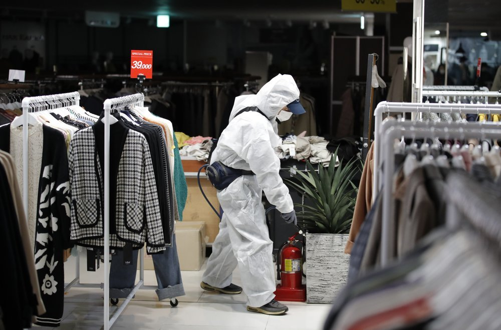 A worker wearing protective gear sprays disinfectant as a precaution against the new coronavirus at a department store in Seoul, South Korea, on Monday. — AP
