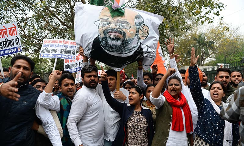 Indian Youth Congress activists shout slogans next to an effigy of Home Minister Amit Shah during a protest demanding his resignation. — AFP