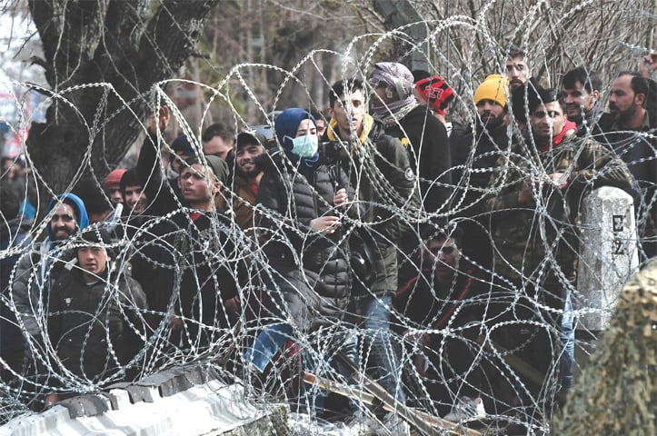 THIS picture taken from the Greek side of the Greece-Turkey border near Kastanies, shows migrants waiting on the Turkish side on Monday.—AFP