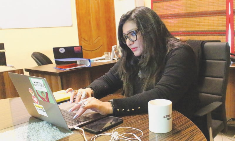 human rights award winner and founder of Pakistan's first  cyber-harassment helpline, Nighat Dad, works on her  laptop at her office in Lahore.—AFP