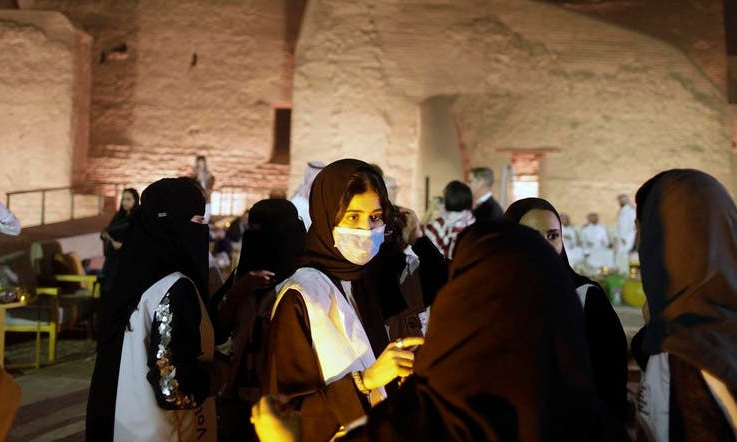 A Saudi tour guide wears a mask, due to the coronavirus, in front of the historical Salwa Palace, in Diriyah, outside Riyadh, Saudi Arabia. — AP