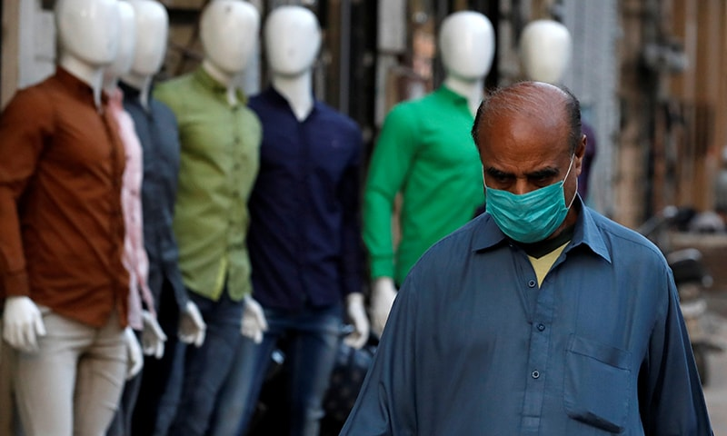 A man wearing a face mask as a preventive measure walks in a market Karachi on Tuesday, March 3. — Reuters