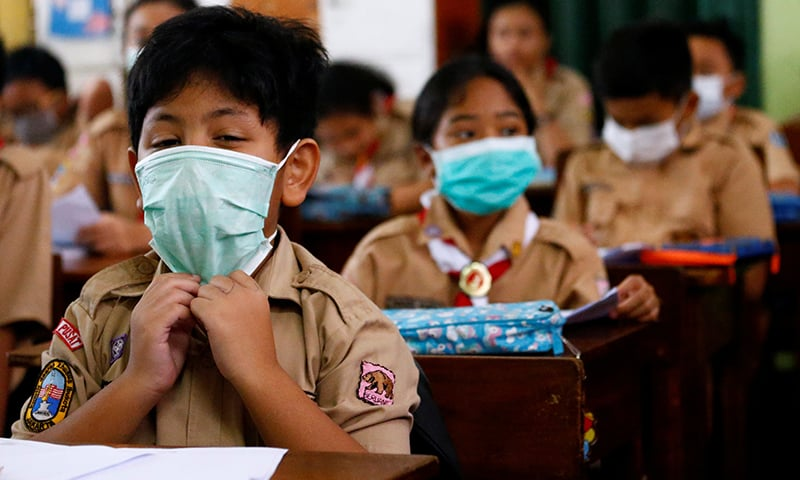 کورونا وائرس سے بچاؤ کے لیے احتیاطی تدابیر اپناتے ہوئے بھارت میں بچوں نے ماسک پہنے ہوئے ہیں— فوٹو: رائٹرز