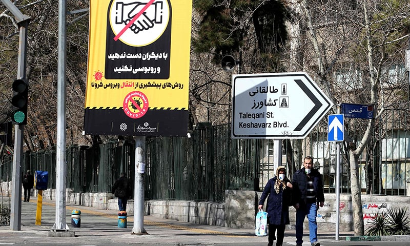 Iranians wearing protective masks walk under a prevention campaign poster for coronavirus on March 4. — AFP
