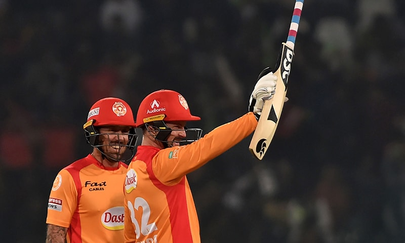 Islamabad United's Colin Munro (R) celebrates after scoring a half century during the PSL T20 cricket match between Lahore Qalandars and Islamabad United at Gaddafi Cricket Stadium on March 4. — AFP