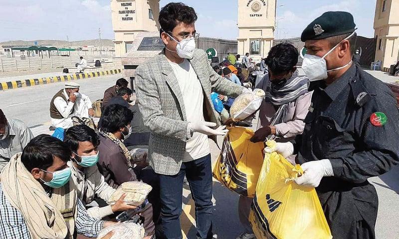 CHAGAI: Assistant Commissioner of Taftan Najeebullah Qambrani distributing food among the pilgrims, who returned from Iran, at Taftan border on Wednesday.—APP