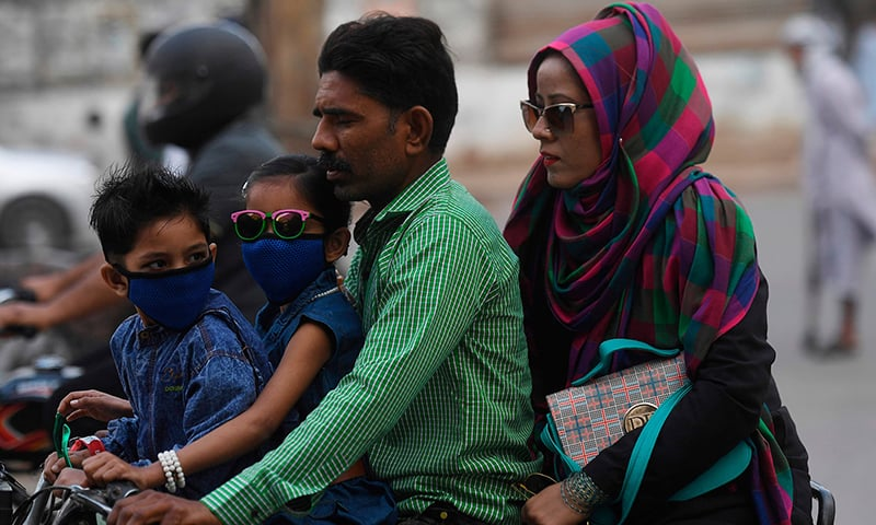 Commuters wear face masks on a street in Karachi on February 28. — AFP/File