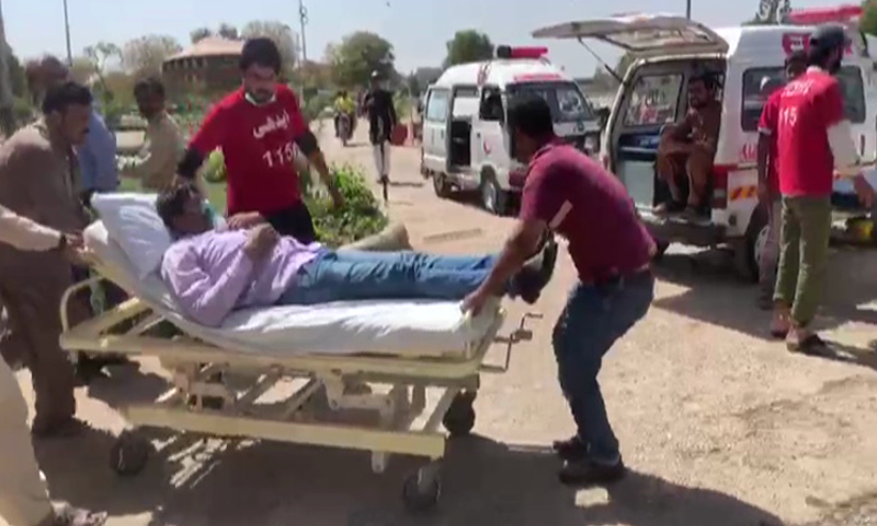 Rescue officials carry a person affected by the gas leak on a stretcher on Friday.— DawnNewsTV