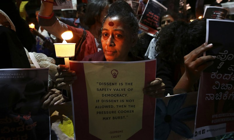 An Indian woman holds a candle and placard during a protest against the sedition case filed by police against a school after a play performed by students denounced a new citizenship law, in Bangalore, India on February 24. Critics, intellectuals, human rights activists, filmmakers, students and journalists seen as being opposed to Modi's government are being increasingly silenced under a colonial-era sedition law. — AP