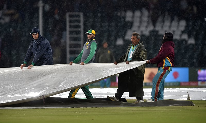 Ground staff members cover the pitch during rain showers during the Pakistan Super League (PSL) T20 cricket match between Karachi Kings and Multan Sultans at the Gaddafi Cricket Stadium in Lahore on March 6. — AFP