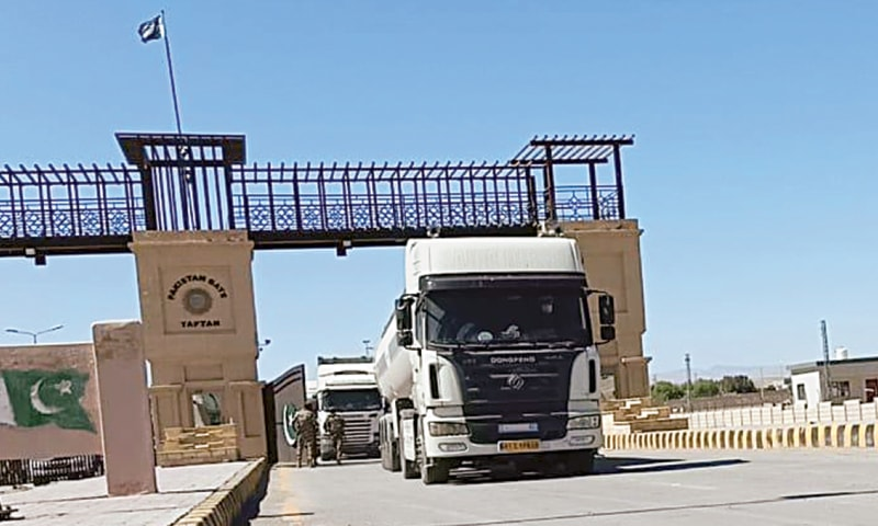 TAFTAN: Iranian vehicles carrying goods pass through Pakistan Gate on Saturday after the border reopened for trade activities after having remained closed for 13 days amid fears of coronavirus outbreak.—Dawn
