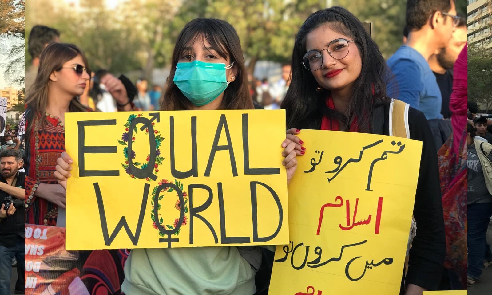 کراچی میں دو لڑکیاں یکساں حقوق کے حصول کیلئے پوسٹر اٹھائے ہوئی ہیں—فوٹو: عائشہ علی