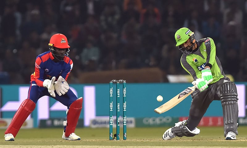 Lahore Qalandars's Sohail Akhtar (R) plays a shot as Karachi Kings's wicketkeeper Chadwick Waltaon looks on during the T20 cricket match between Karachi Kings and Lahore Qalandars at the Gaddafi Cricket Stadium in Lahore on March 8, 2020. — AFP