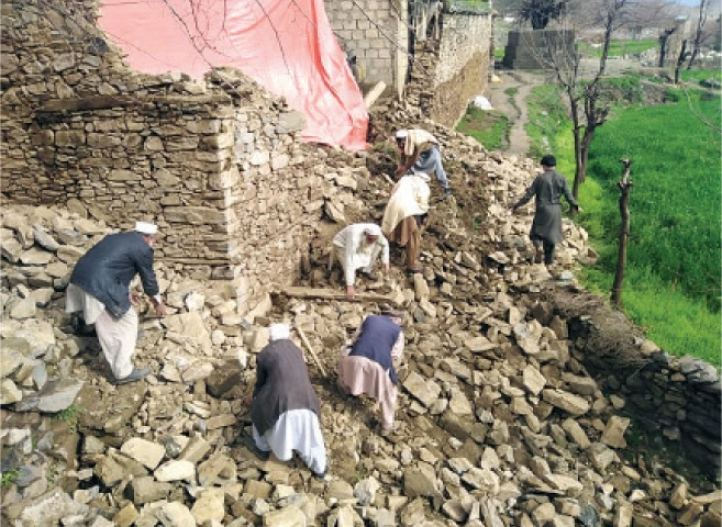 Locals remove the rubble after roof of a house collapsed in Bajaur on Sunday. — Dawn