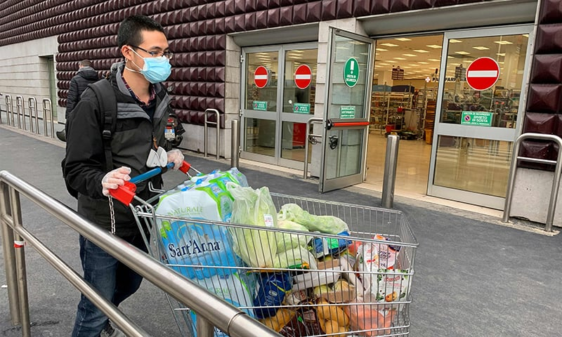 A man wearing a protective mask leaves a supermarket with trolleys full of shopping in Milan on March 8 as Italy quarantines more than 10 million people around the financial capital Milan and the tourist mecca Venice for nearly a month to halt the spread of the novel coronavirus, COVID-19. — AFP