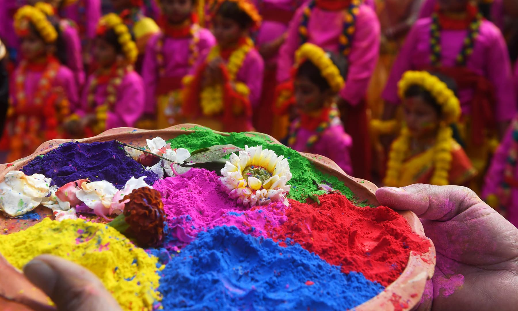 A participant holds a tray of coloured powder as students take part in a cultural procession to celebrate Holi, the spring festival of colours, in Kolkata, India on March 9. — AFP