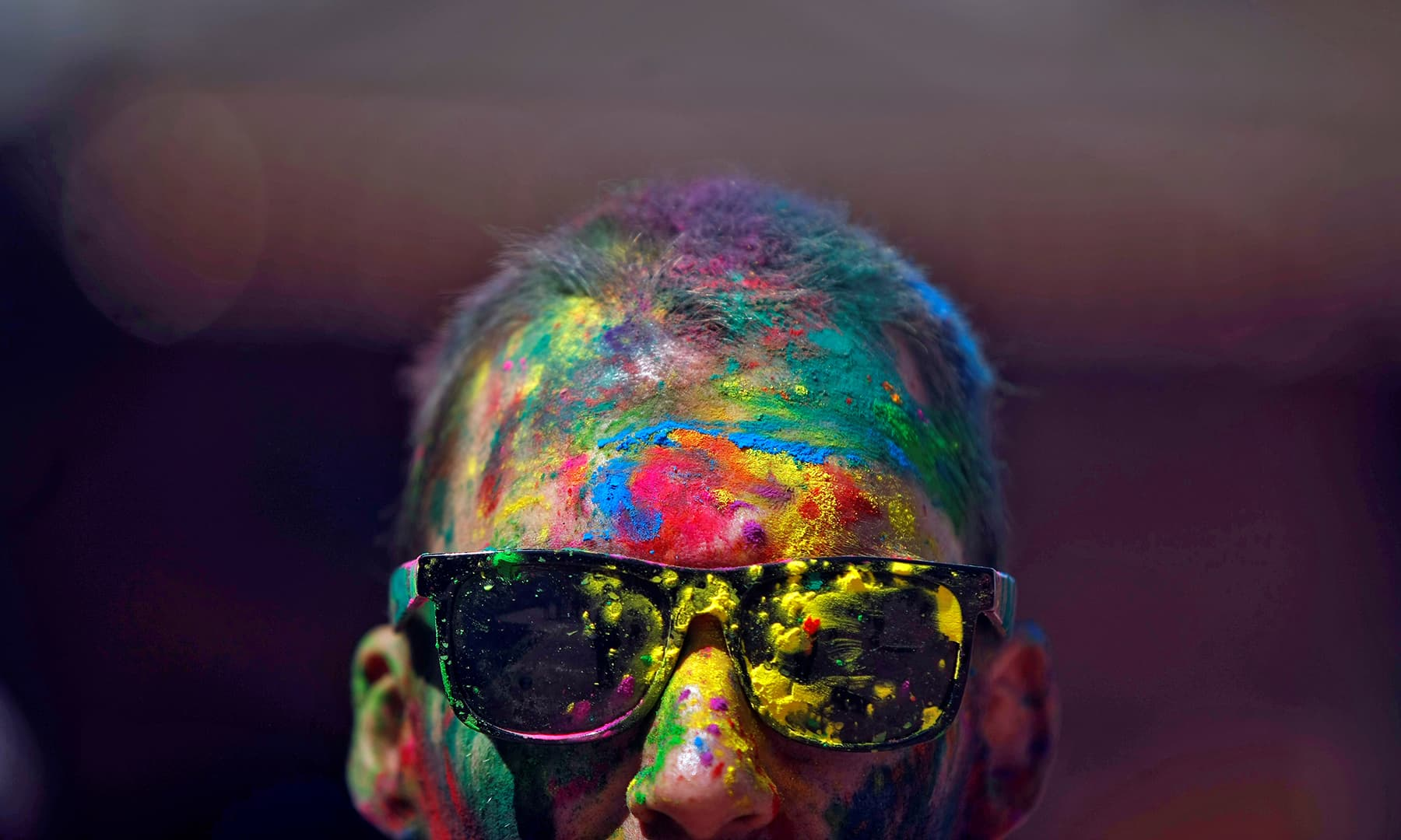 A man with coloured powder smeared on his face and head is pictured while celebrating Holi in Kathmandu, Nepal. — Reuters