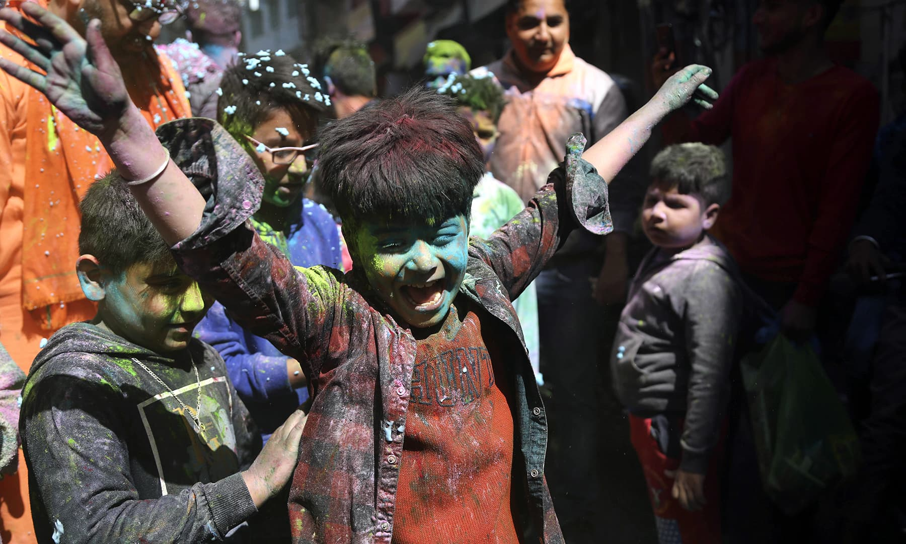 Children dance and throw coloured powder during Holi celebrations in occupied Jammu, India. — AP