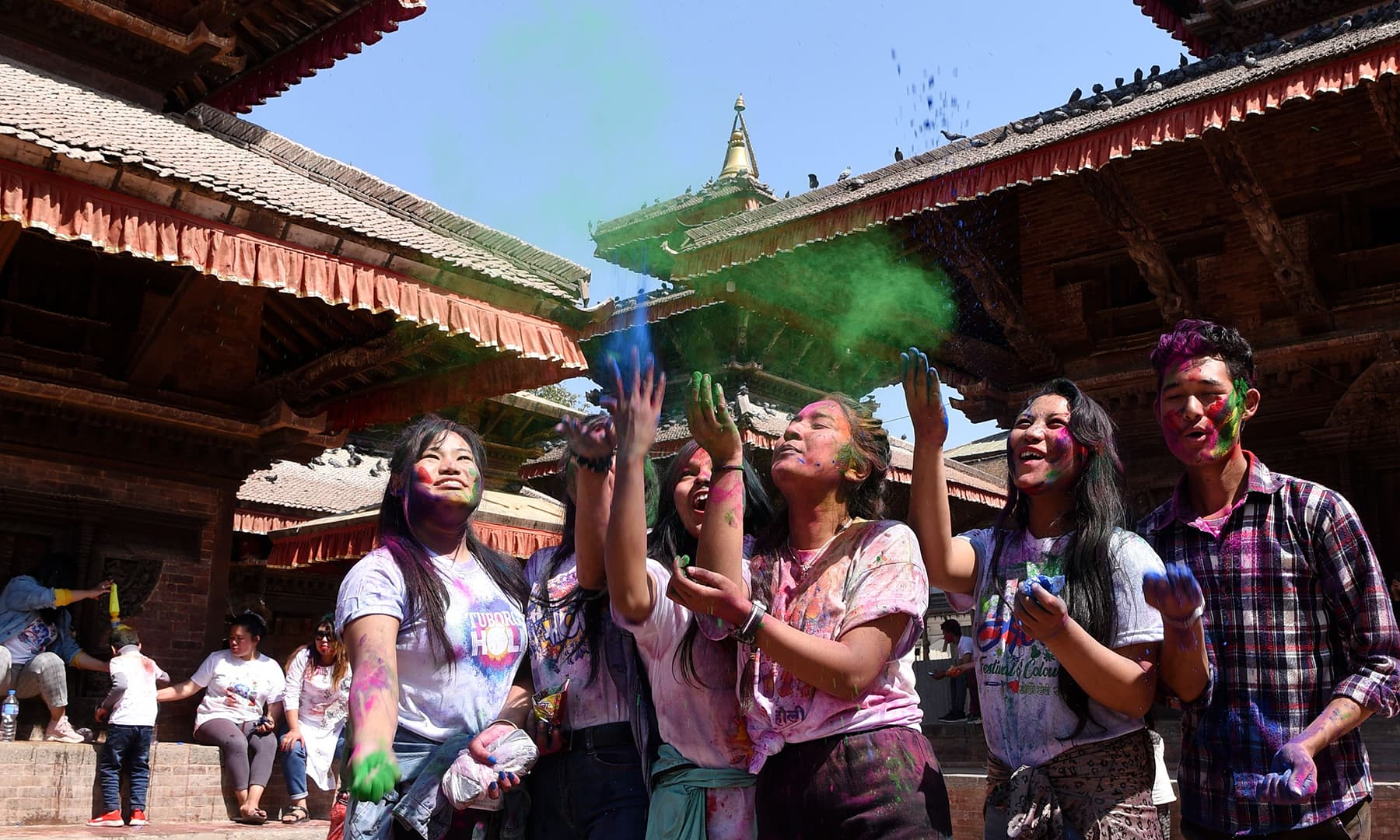 Revellers play with coloured powder as they celebrate Holi in Kathmandu on March 9. — AFP