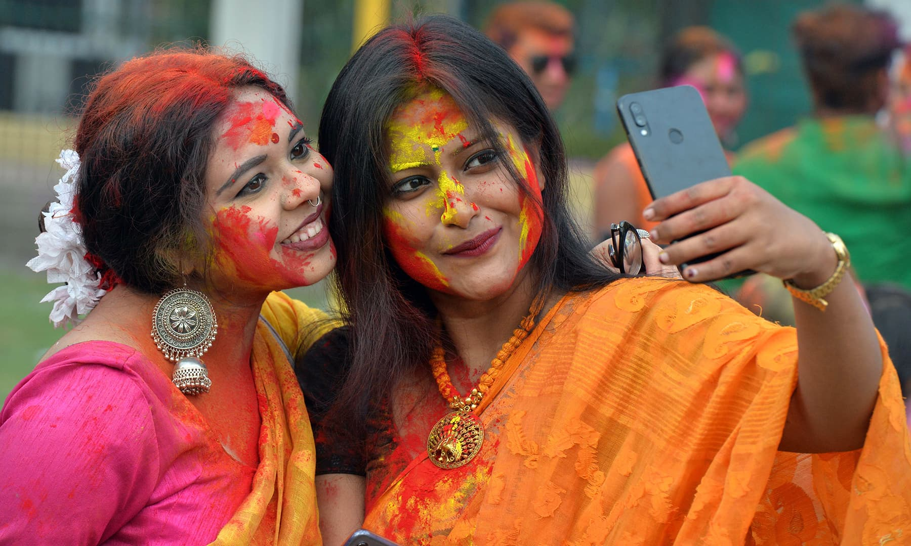 Revellers with their faces smeared with colour powder take a selfie as they celebrate Holi in Siliguri on March 9. — AFP