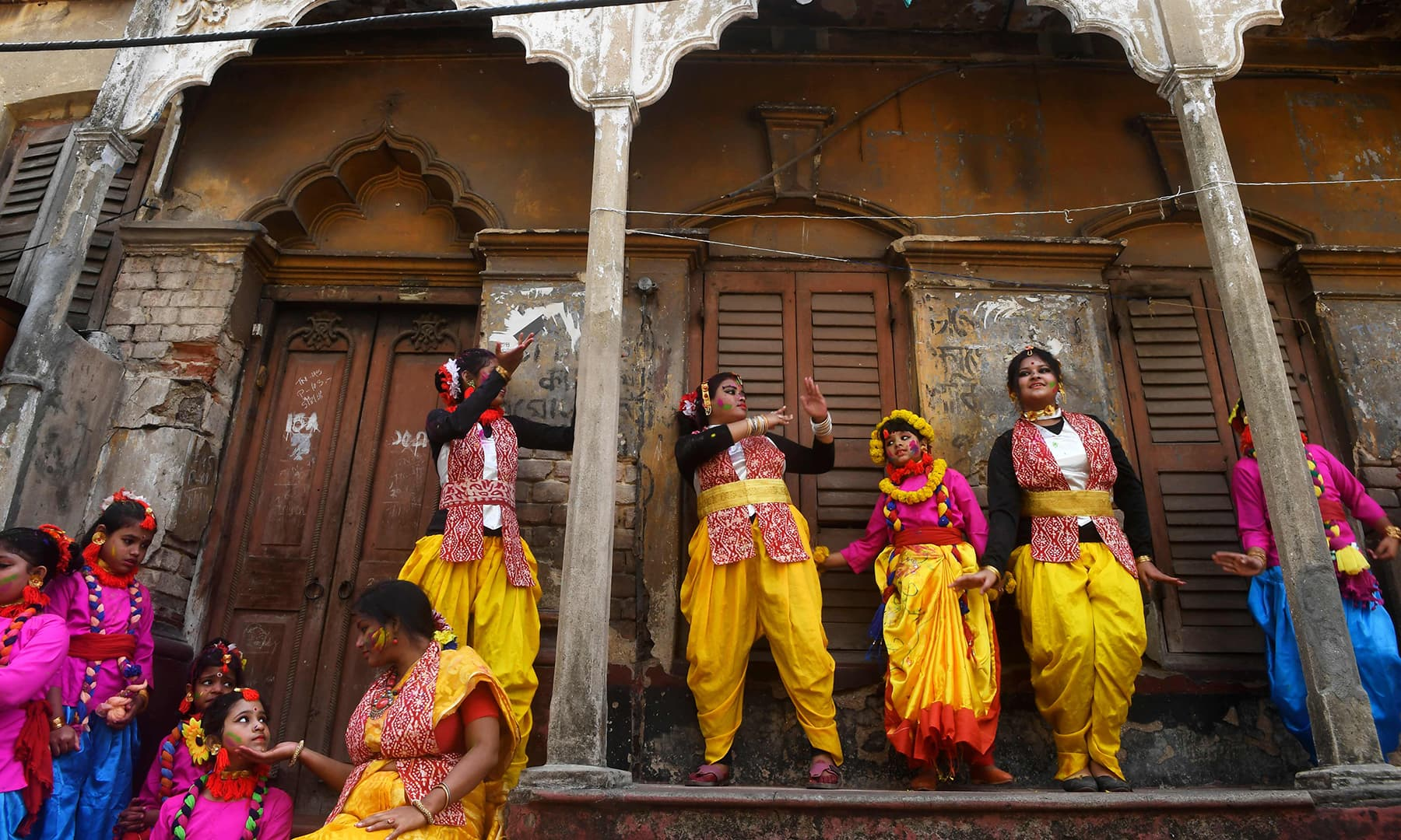 Students and others take a break during a cultural procession to celebrate Holi in Kolkata. — AFP