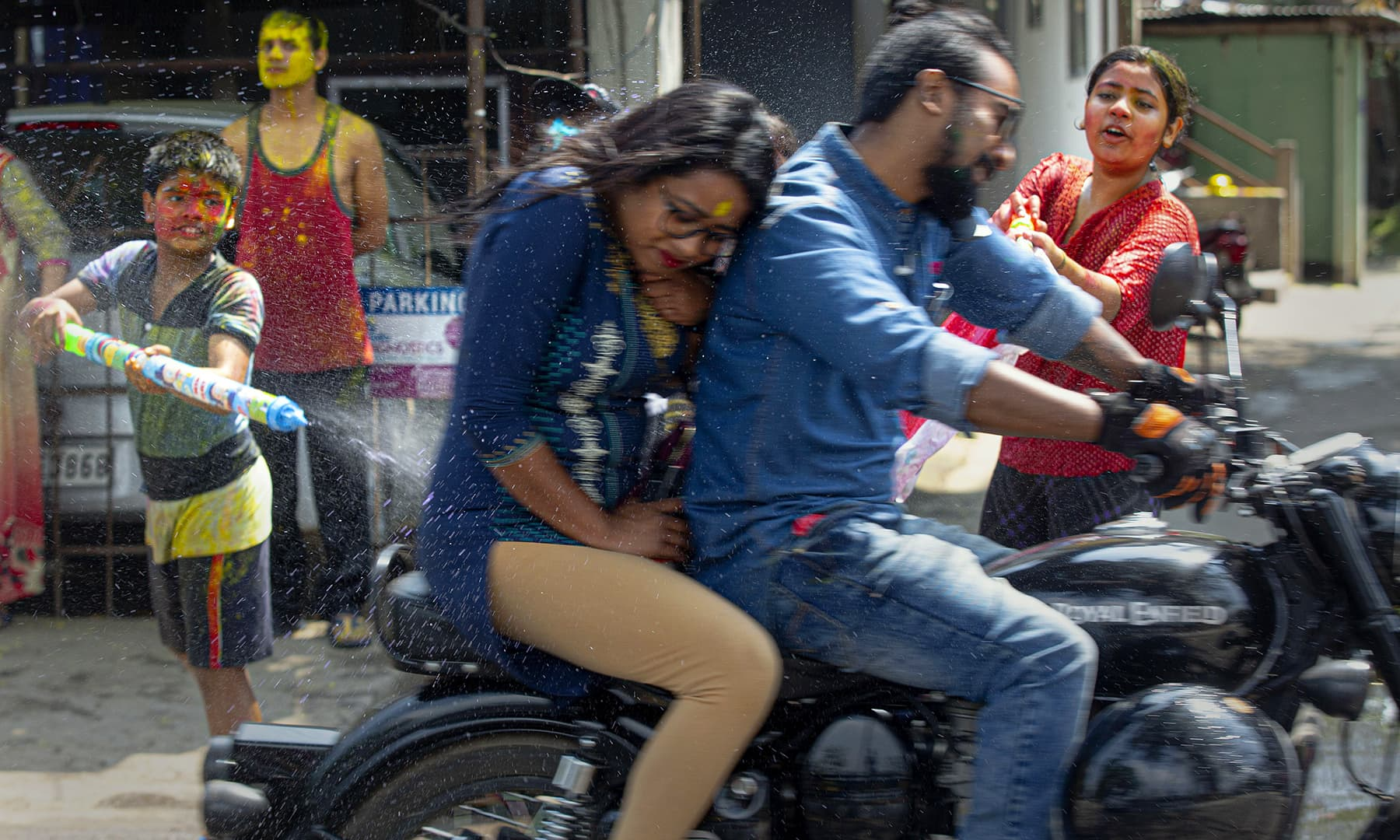 Indian children spray colours on to a couple riding a motorcycle as they celebrate Holi festival in Gauhati, India, Monday. — AP
