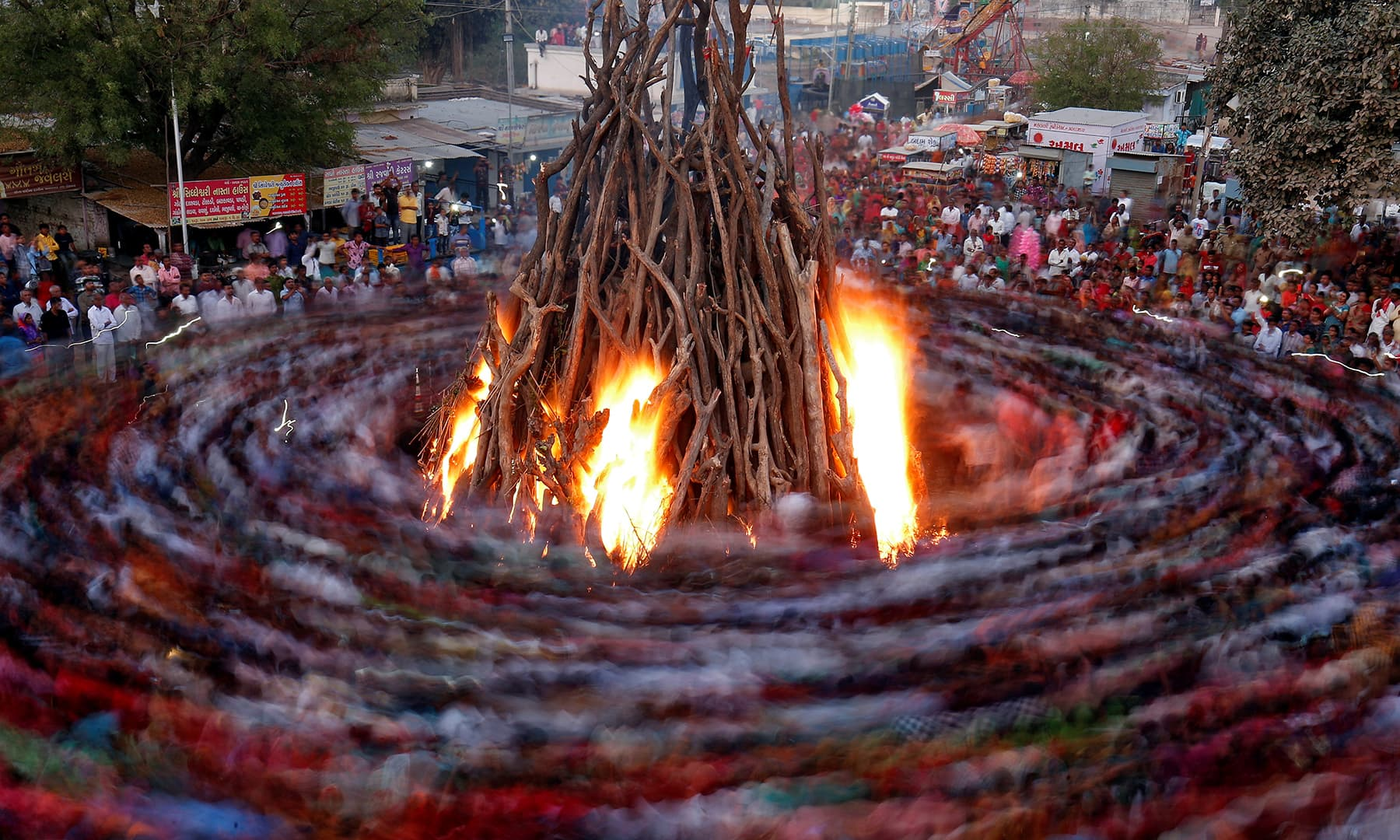 """Hindu devotees walk around a bonfire during a ritual known as """"Holika Dahan"""" which is part of Holi festival celebrations in Ahmedabad, India. — Reuters"""