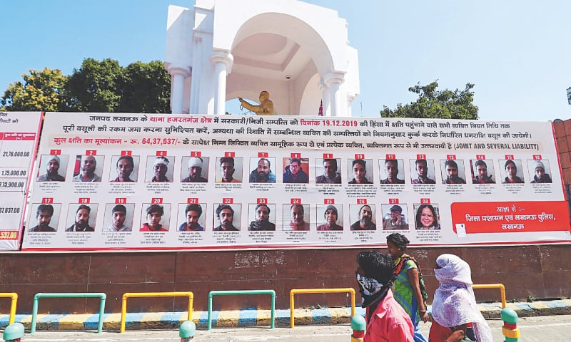Lucknow: Commuters walk past a billboard displaying pictures, names and addresses of people accused of vandalism during deadly protests in December against India's citizenship law.—AFP