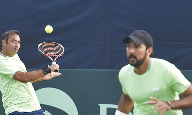 Pakistan's Aqeel Khan hits a return as his partner Aisam-ul-Haq looks on during their doubles match in the Davis Cup tie against Blaz Kavcic and Tom Kocevar of Slovenia on Monday. —Tanveer Shahzad/White Star