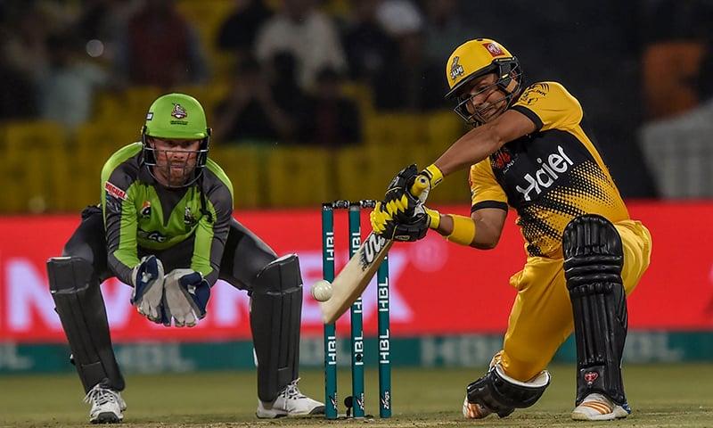 Peshawar Zalmi's Kamran Akmal (R) plays a shot next to Lahore Qalandars' Ben Dunk (L) during the T20 cricket match at the Gaddafi Cricket Stadium in Lahore. — AFP