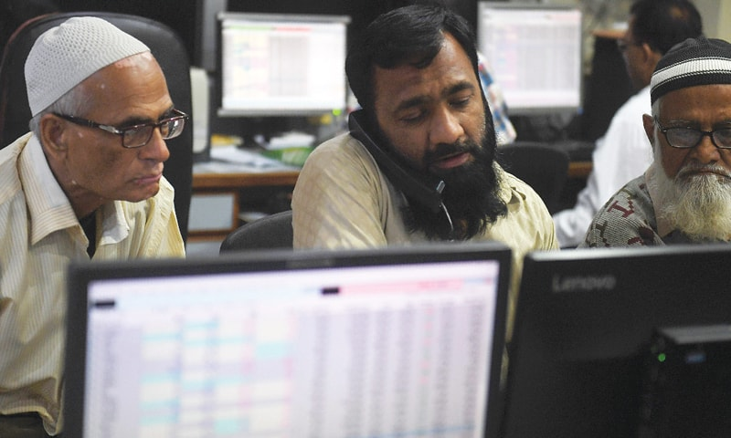 KARACHI: Stockbrokers mointor share prices during a trading session at the Pakistan Stock Exchange  on Tuesday.—AFP