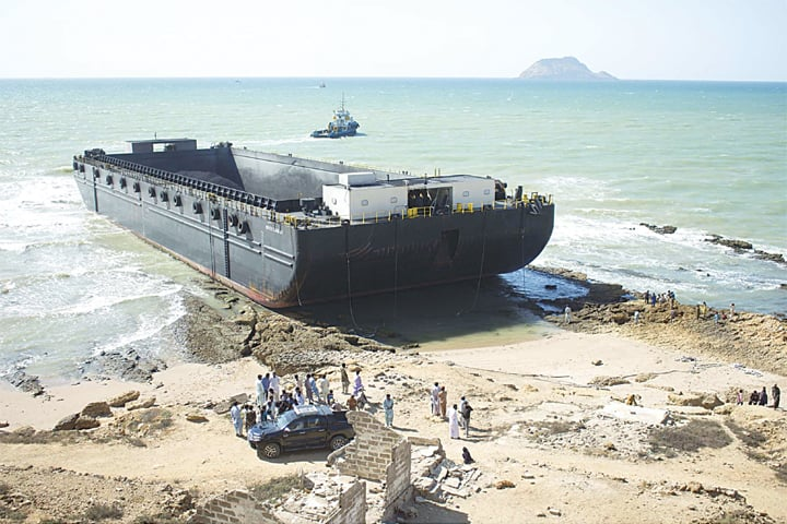 KARACHI: A vessel carrying coal cargo is pictured after it ran aground near Mubarak Village on Wednesday. The ship ran aground after big sea waves steered it from its route towards a rocky surface of the beach in the morning.—PPI